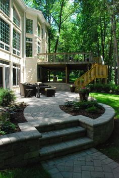 Large deck and patio, with a path that leads into the woods with a fire pit. The Vande Hey Company, Inc.