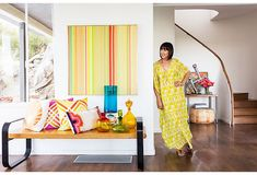 """A vintage bench is topped with an array of Trina's own pillows, colored glass vessels, and an estate-sale score. """"This striped painting is not done by anyone noteworthy but feels high-end,"""" she says."""