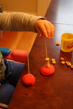 """lace"" Cheerios onto dry spaghetti stuck in play-doh for a great sensory and fine motor activity"