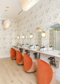 In the beauty room, floral wallpaper from Caitlin McGauley picks up the tangerine color of the chairs from Douglas & Bec. Wall light sculptures from Cedar & Moss illuminate the mirrors. #washingtondc #office #colorful #pastel #womenrun