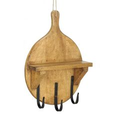 Decorate your kitchen with some whimsy! This mango wood wall shelf is shaped like a pizza paddle used in wood-fired grills. It has a display shelf and three large hooks below that you can use to hang