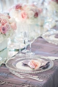 Lavender linens with garden rose on each plate.