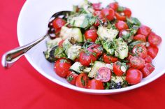 Grilled Zucchini and Grape Tomato Salad  1 large zucchini  Extra virgin olive oil  1 pint grape tomatoes  Handful fresh herbs — chives, sage, basil, summery savory, oregano  1 tablespoon extra virgin finishing-quality olive oil, or more to taste  1 teaspoon balsamic vinegar  1/2 teaspoon flaky sea salt  Freshly ground black pepper, to taste  1 tablespoon Parmesan cheese