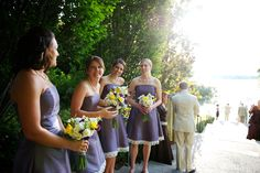Bridesmaids bouquets of white and yellow freesia, white roses, and purple sweat pea