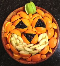 Jack-o'-lantern Pumpkin Fruit Tray.  Sliced oranges, sliced apples & blueberries arranged in a round bowl to make look like a jack-o'-lantern for Halloween.  Healthy snack option for kids or fun party food.