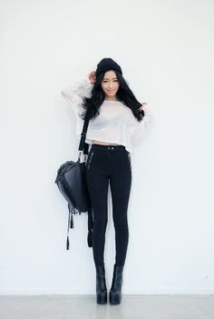 Cute black and white winter outfit with the white cropped long sleeve, black high waisted pants, black heeled boots, black shoulder bag, and a black beanie