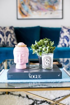 A blue velvet sofa brightens am otherwise neutral living room. Love the coffee table styling!
