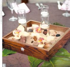 Zen-inspired centerpieces created inside oak boxes, filled with candles, Japanese river rocks, and orchids