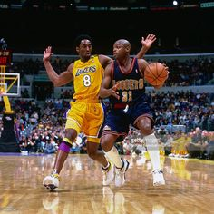 Nick Van Exel #31 of the Denver Nuggets drives to the basket against Kobe Bryant #8 of the Los Angeles Lakers circa 2001 at Staples Center in Los Angeles, CA.