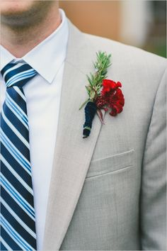 gray suit with blue striped tie and cockscomb red and rosemary boutonniere