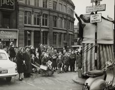 A photograph of a crowd of people watching a Punch and Judy show in Liverpool, taken in 1957 by Ralph for the Daily Herald.