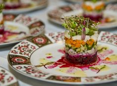 Timbale of roasted beet root, onions, pickled cucumbers, potatoes,  carrots + herring, crowned with dressed micro greens