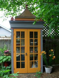 Potting shed, which resembles a charming little old phone booth, great for all garden tools. Love this!