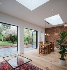 Open plan living at its best. Love the wood flooring bi-folding doors roof lights and exposed brick wall. Red Brick Walls, Exposed Brick Walls, Kitchens With Brick Walls, Exposed Brick Kitchen, Brick Wall Kitchen, Kitchen Diner Extension, Kitchen Extension Skylights, House Extension Design, Patio Extension Ideas