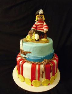 Pirate Birthday Party! Pirate cake! Pirate Party! Details include gold coins, traditional red and white stripes, braided rope, ship on the ocean, and topped with a pirate sitting on a treasure chest.