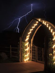 A Lightning Bolt Comes Out of Night Sky Near a Decorated Gate by Robbie George