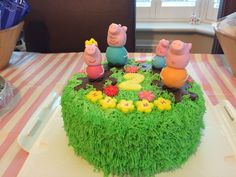 Peppa pig chocolate birthday cake with buttercream grass and Peppa pig and family jumping in muddy puddles.