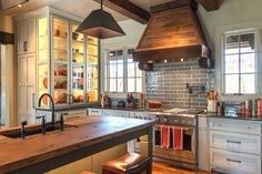 Glass-front cabinets in the kitchen lighten up the room and also make the most of space, since they span ceiling to countertop. A vent hood made of reclaimed wood adds an organic touch to the range area.