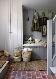I love the farmhouse style of this mudroom... colors, closed storage, bench, hanging storage