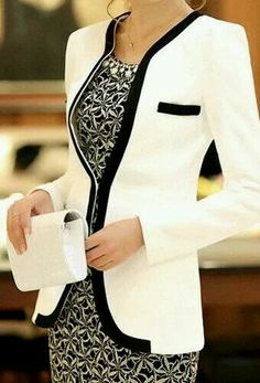 Elongated cream colored blazer, edges trimmed in a wide band of black. Breast pocket trimmed in black as well. Square shoulders and long sleeves. Worn over a dress with white and black abstract mosaic print. Cream clutch. Lovely line. Style Planet