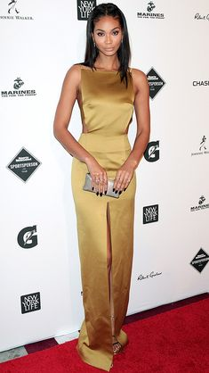 CHANEL IMAN in an olive gown with a thigh-high center slit