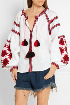 MARCH11's blouse is modeled after the traditional 'Vyshyvanka' Ukranian costume, believed to symbolize protection. Crafted from white linen, it's embroidered with a red and black geometric motif and finished with large tassels and billowing sleeves. Style this statement piece with denim shorts.