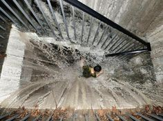 Photograph by China Daily/Reuters    CHINA    Rainwater cascades onto a Chengdu resident rushing up a flight of stairs from an underground garage. An unusually severe downpour on July 3, 2011, flooded streets and knocked out electricity in the city, which is the capital of Sichuan Province in central China.