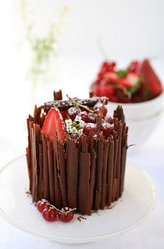 Chocolate mousse cake enrobed in chocolate curls and topped with Strawberries or raspberries.. http://www.marthastewart.com/317890/triple-chocolate-mousse-cake
