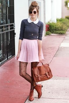 a different take on preppy. The dark sunglasses and black tights give her a little more edge. love the satchel.