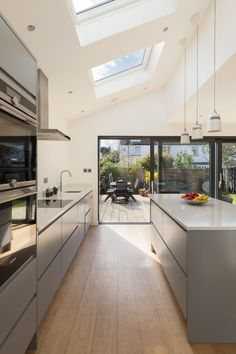 A modern side kitchen extension with large feature sliding doors onto a rear timber decking Best Modern Kitchen Lighting Ideas and Tips design with island Small Kitchen Lighting Ideas Pictures for Low Ceilings - HARP POST Open Plan Kitchen Living Room, Home Decor Kitchen, New Kitchen, Kitchen Lamps, Kitchen Cabinets, Kitchen Time, Kitchen With Window, Grey Cupboards, Open Plan Kitchen Diner