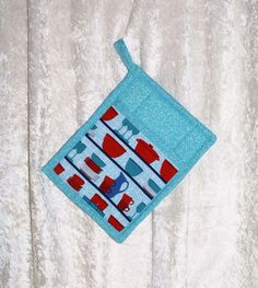 Handmade pot holder featuring designer fabric in vibrant tableware icons and a coordinating turquoise pattern adds fun to your kitchen. This