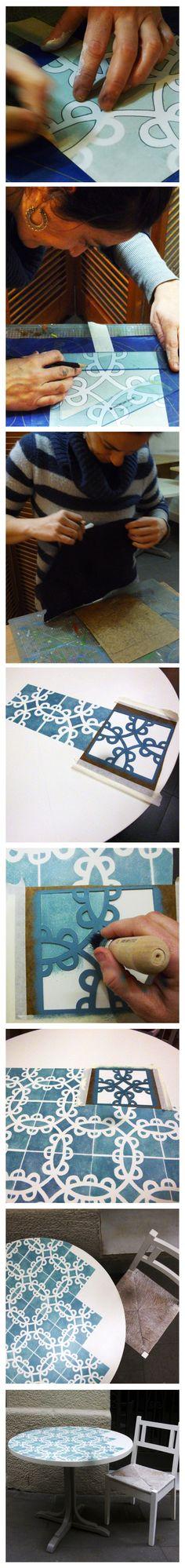 #ElsMoblesDeLaMai -Taula Rajola, Taula de menjador rodona de fusta. Potes lacades en color gris pedra i sobre decorat amb motius de rajola hidràulica en blanc i gris-blau.