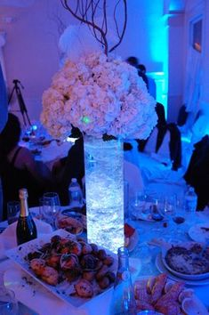Wedding Centerpiece idea using a Tall Clear Cylinder and Hydrangea arrangement. Try filling your simple container with Aqua Crystals and submersible LED lights to make it pop. #AquaCrystals #FlourishingFlowerTowers #VesselsAndVases https://www.WedCrafts.com Amanda@WedCrafts.com