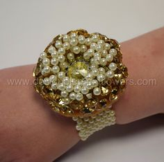 This stunning handcrafted wrist corsage Couture Gold Diamante , Pearls with Gold Diamante Brooch which is designed on a Ivory Pearl Bracelet. www.designelementflowers.com