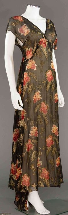 """PRINTED & LAME CHIFFON GOWN, 1930s  Lot: 194 May 9, 2017 - CATALOG SALE Sturbridge, Massachusetts  Black silk chiffon w/ printed rose nose-gays & woven gold lame leaves, trained & sleeveless, B 33"""", W 25"""", H 36"""", L 54""""-61"""", (right arm hole tarnished, pin holes at CB) very good."""
