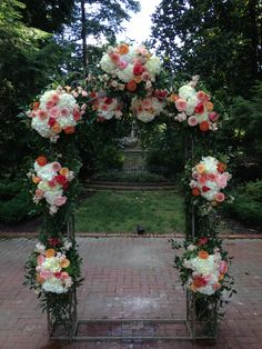 Arch of peach, coral and white flowers.  www.hollidayflowers.com