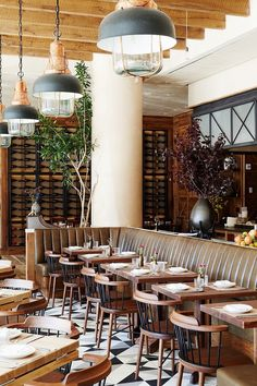 Restaurant space with wood and neutral elements, exposed beams, and industrial pendant lights