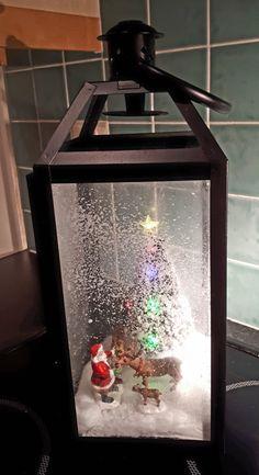 Handmade Christmas scene lantern. Santa feeding his reindeer.