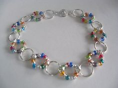 Colorful Seed Bead and Silver Bracelet - This is a beautiful, colorful and causal bracelet. Perfect for everyday. The bracelet measures 7 1/2 inches in length. Each link is a 10mm silver plated jump ring, alternating between plain silver and one filled with 3mm colorful seed beads. The clasp is a secure button clasp for easy on and off.