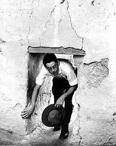 Casa Grand Ruins National Monument - 1934 - Although the inhabitants of Casa Grande were of average hieght, low doorways were built for purposes of defense. One man standing at each doorway, armed with a club could successfully defend the room from beseigers. North wall of east room.