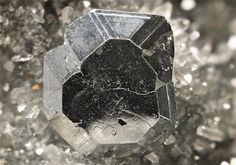 A bright well-formed metallic grey tabular crystal of Bournonite measuring to 8mm sits neatly at the centre of the Quartz druse specimen, from the Příbram mining area in the Czech Republic. Crystal Classics Minerals