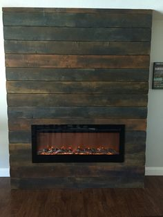 Reclaimed wood look for fireplace. Used new tongue and groove boards, beat them up and stained them. Electric fireplace insert.