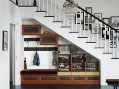 rangement sous escalier dans l'entrée de maison avec porte-manteau, banc et rangements cubes