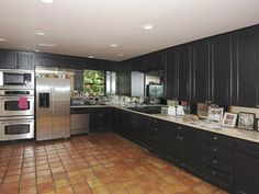 Love this dark grey kitchen! It looks so sleek and luxe with steel appliances and terra cotta tile. #design #decor #home
