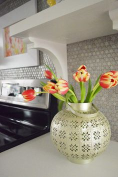 Tin lantern found at HomeGoods used as a vase! Great idea by blogger Sherry from Young House Love!
