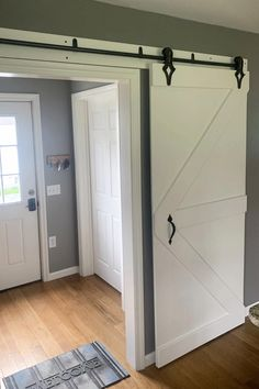 White farmhouse sliding barn door from living room to foyer entrance hall. Love the rustic look and gray wall paint - those wood floors are gorgeous too! Diy Sliding Barn Door, Diy Barn Door, Diy Door, Barn Doors, Sliding Wall, Sliding Doors, Wall Painting Living Room, Grey Walls Living Room, Living Room Modern