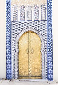 Golden door in blue tiled doorway. Morocco