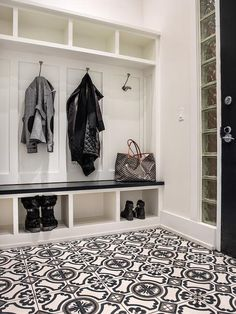 Fabulous mudroom boasts a row of open cubbies above open lockers lined with coat hooks as well as a mudroom bench fitted with shoe shelves alongside a black and gray mosaic tiled floor.