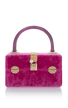 This deliciously cute bag by **Dolce & Gabbana** features a entirely velvet construction with gold hardware finished by a python printed top handle.