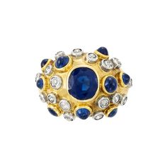 Gold, Platinum, Sapphire and Diamond Ring, France 18 kt., the bombe mount centering one bezel-set modified oval sapphire, surrounded by 16 platinum-set old-mine cut diamonds approximately, and 9 collet-set round cabochon sapphires, with French assay mark, circa 1940.